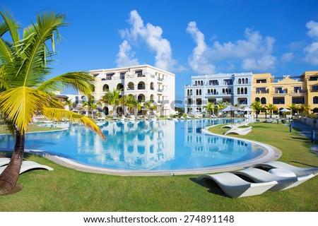 Swimming pool by the luxury resort hotel buildings