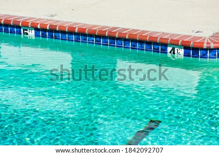 Swimming pool depth markers on pool edge identify the water depth for swimmers. Four and one half feet, and five feet depth signs. Stock photo ©
