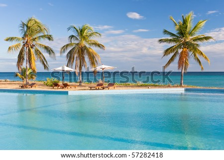 Swimming pool facing the lagoon in a tropical hotel - stock photo