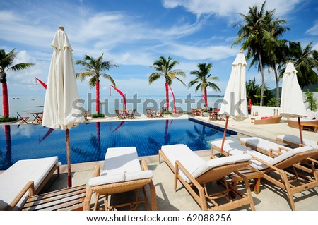 Swimming pool facing the lagoon in a tropical hotel with coconut & beach Samui Thailand