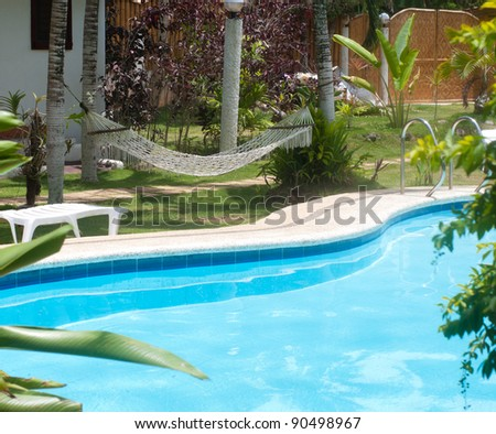 swimming pool in a tropical garden with hammock