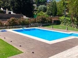 Swimming pool in home garden with wooden floor
