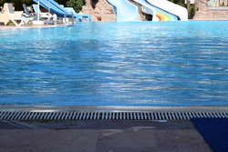 Swimming pool in touristic resort during summer time. Aqua Park with water slides and a large swimming pool. Relaxation and sunbathing area of the hotel