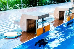 Swimming pool jump platform with kickboard beside background. Concrete diving platform or jumping start stand with foam buoy and swimming lane number 5