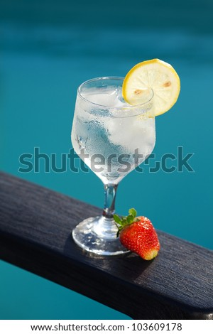 Swimming pool, lounge, a wine glass with ice, lemon and strawberry
