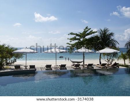 Swimming-pool near the beach at luxury, tropical resort hotel.