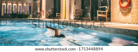 Swimming pool of condo buildings re-opening after COVID-19 confinement. Swimmer woman doing crawl in public pool banner panoramic.