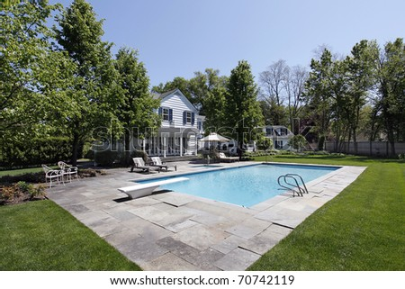 Swimming pool outside luxury home with diving board