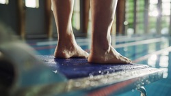 Swimming Pool: Professional Swimmer Standing on a Starting Block. Overcoming Fear, Determined Athlete Ready to Set New Record on a Championship. Stylish Cinematic Focus on Legs. Close-up Shot