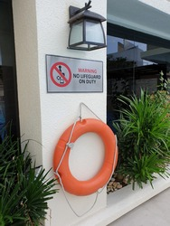 Swimming pool rescue and safety ring is hang at wall for emergency uses.