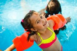 Swimming pool slides for children on water slide at aquapark . Summer kid holiday outdoor. Little girl in aqua park.