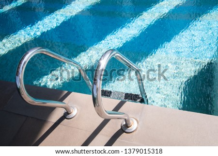swimming pool stair in blue water at hotel .