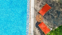 Swimming pool with blue water and sunbed deckchairs aerial top view, tropical vacation hotel resort from above