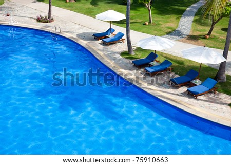 Swimming pool with chaise lounge and sunshade at tropical resort
