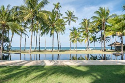 Swimming pool with coconut tree and sea background, reflection of coconut trees and white cloud and blue sky on the swimming pool at the beach