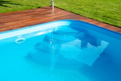 Swimming pool with Ipe wood deck and green grass. Exotic hardwood Ipe decking beside swimming pool close up