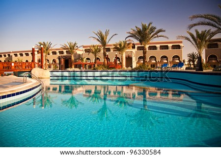 swimming pool with palm trees at morning, Hurghada, Egypt