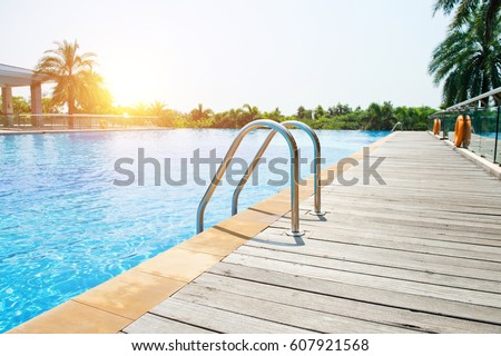 Swimming pool with stair and wooden deck at hotel.