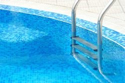 Swimming pool with stair at hotel close up