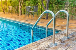 Swimming pool with stair at hotel with decorated with trees and chairs for relaxing