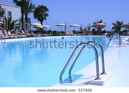 Swimming pool with steps, palms and parasols