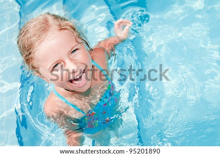Swimming, summer vacation - lovely girl playing in blue water