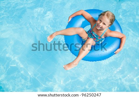 Swimming, summer vacation - lovely girl playing in blue water (space for text)