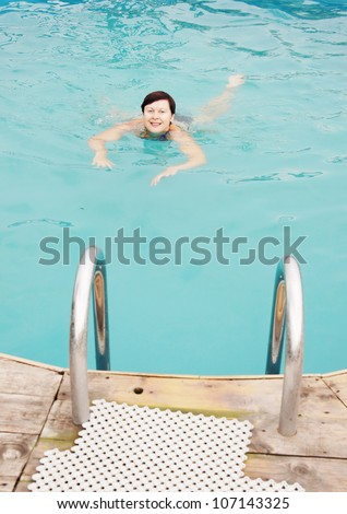 Swimming woman in an outdoor pool (focus on the woman) #107143325
