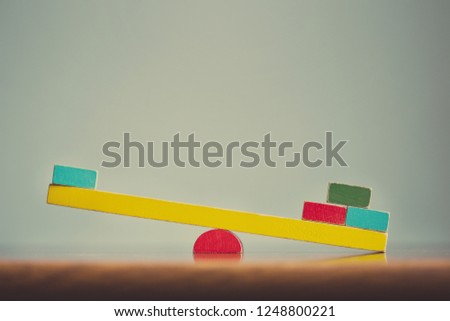 swing balancer for two built of wooden cubes. overweight. concept information asymmetry. Foto stock ©