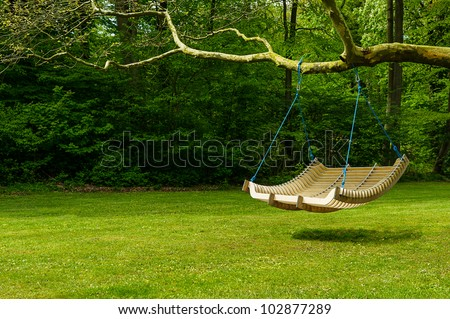 Swing bench in lush garden. Curved swing bench hanging from the bough of a tree in a lush garden with woodland backdrop for relaxing on hot summer days