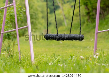Swing in a garden with no children, pink construction and black swing #1428094430