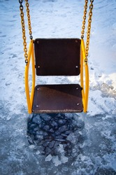 swing on a chain and an ice hole with water in winter. Extreme attraction. A hole in the ice on the playground.