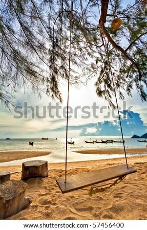 Swing on a tropical beach against the setting sun