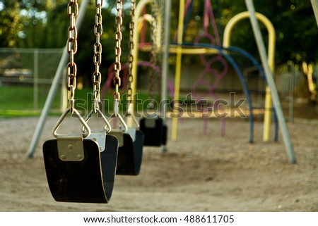 Swing set at a playground that is empty. Lighting is warm due to the being taken at sunset