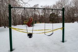 Swing set in a children's playground with trees in the distance.  The set is made of metal and has two swings. One is for infants and the other for young children. The bases are made of black rubber.