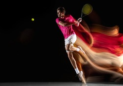 Swinging volley. Young caucasian man, male tennis player in white pink sportwear playing tennis in mixed light on dark background. Concept of motion, power, speed, healthy lifestyle, professional