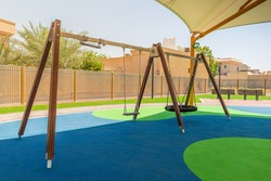 Swings in Dubai's public park, regular and nest type, above the rubber floor covered with the tensile shade canopy, summertime