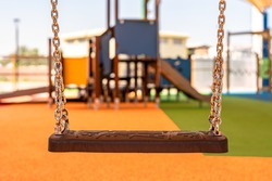Swings in Dubai's public park, regular rubber seat suspended on chain links, above the rubber floor covered with the tensile shade canopy, summertime