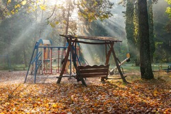 Swings on children playground under sun rays. Beautiful misty and sunny morning autumn scenery in the park.