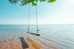 Swings under the shade of trees and tranquil seaside beaches