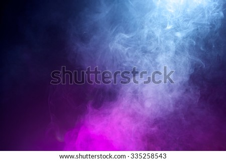 Swirling fog lit with pink and blue gels to create a multicolored background texture.  - Shutterstock ID 335258543