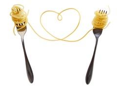 Swirls of cooked spaghetti with fork. Spaghetti heart shape.
