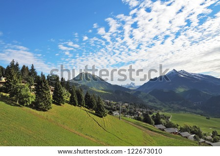 Swiss Alps. Green alpine meadow on a hillside and surrounded by pine forests