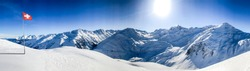 swiss alps mountain panorama in winter snow with the swiss flag on a sunny day with blue sky in the ski area gstaad