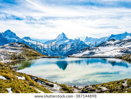Swiss alps water reflection in Bachalpsee lake  above Grindelwald, Switzerland. #387144898