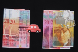 Swiss banknotes, house-shaped keychain and car-shaped paperclip, Happy New Year, numbers 2020 and 2021 made up of banknote denominations accumulated for new own housing in 2021