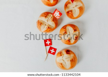 Swiss bread buns called in German 1. Augustweggen baked in Switzerland to celebrate Swiss National Day on August 1st. Swiss flag with white cross on red. White background, isolated, copy space.