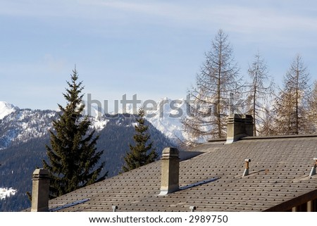 Swiss chalet roof under mountains