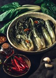 Swiss chard (Bietola) recipe with hot peppers, garlic, wine vinegar, herbs and olive oil on the dark rustic background. Seasonal vegetarian cuisine. Vegan food cooking preparation