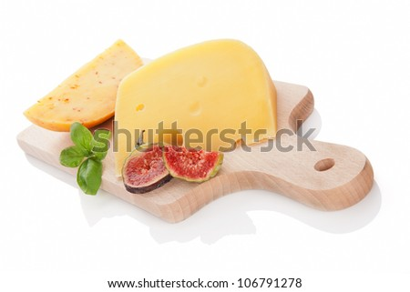 Swiss cheese and gouda piece on wooden cutting board isolated on white background decorated with fig and fresh basil. Luxurious cheese still life.